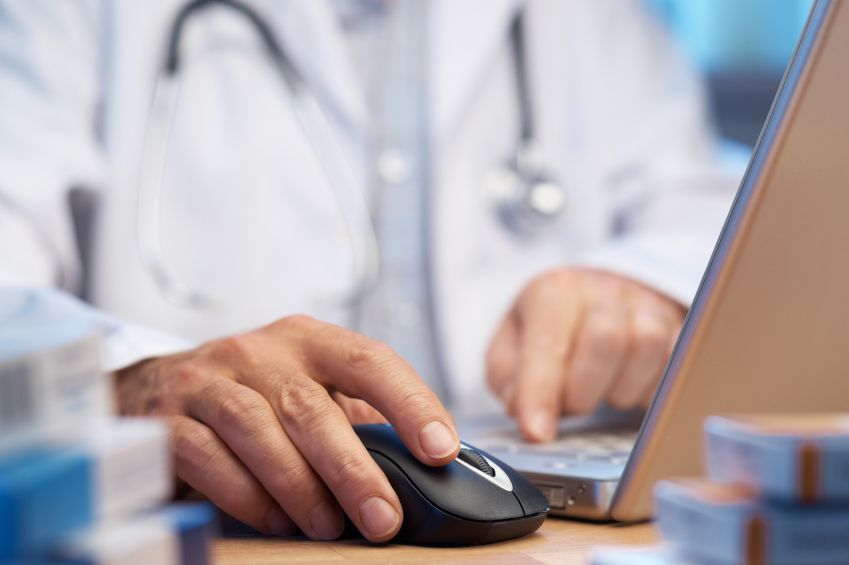 Doctor typing medical bill in computer